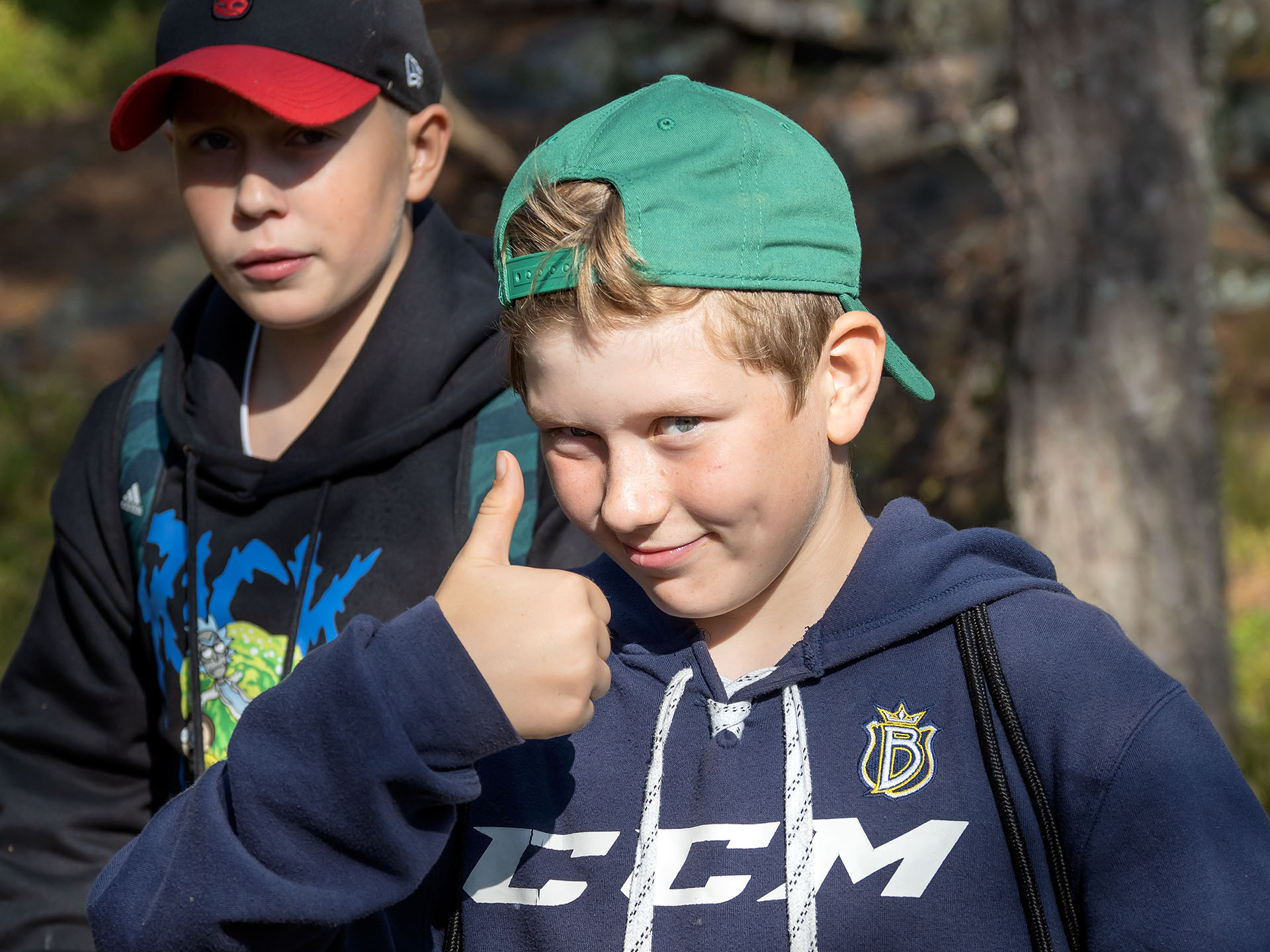 En skolpojke visar tummen upp ute i naturen.