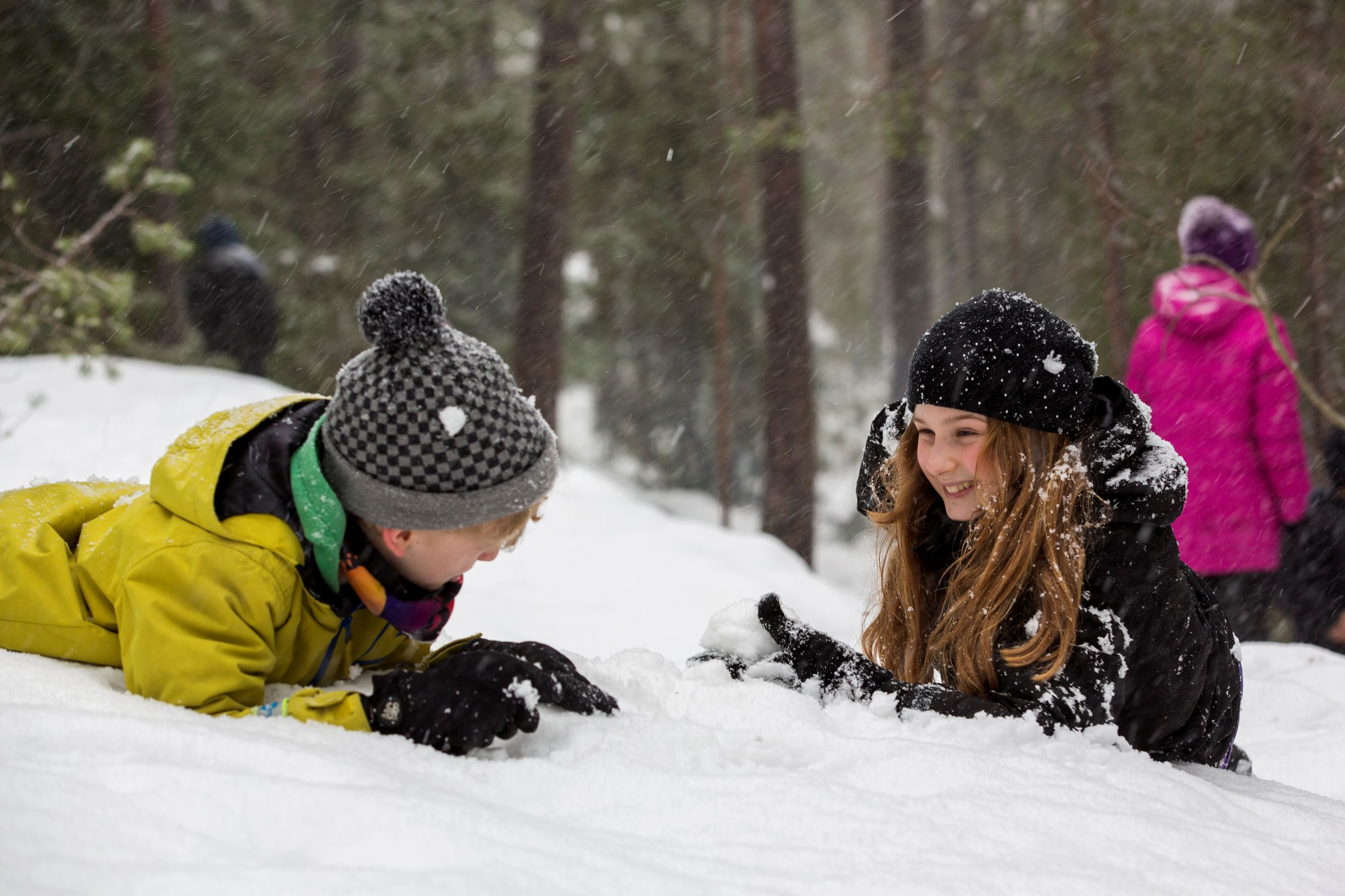 Lapset leikkivät lumisotaa.