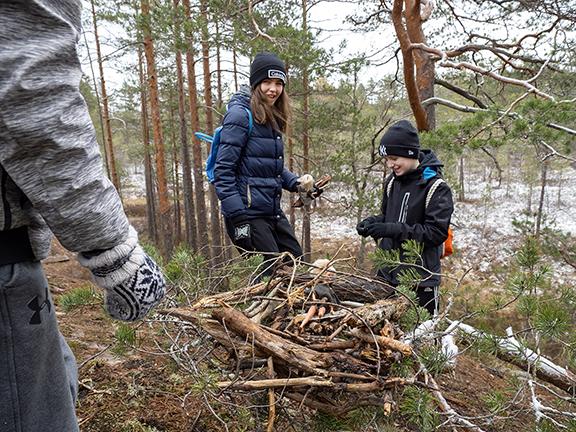Koululaiset tekevät kepeistä rakennelmia metsässä