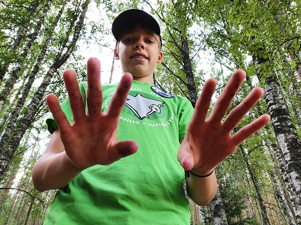 Nuorella pojalla päällä Nuuksion kansallispuiston t-paita päällä metsässä