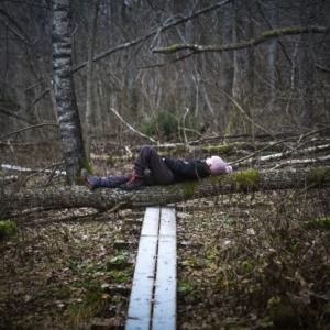 Ihminen makaa kaatuneen puun päällä. En människa ligger på ett fallet träd.