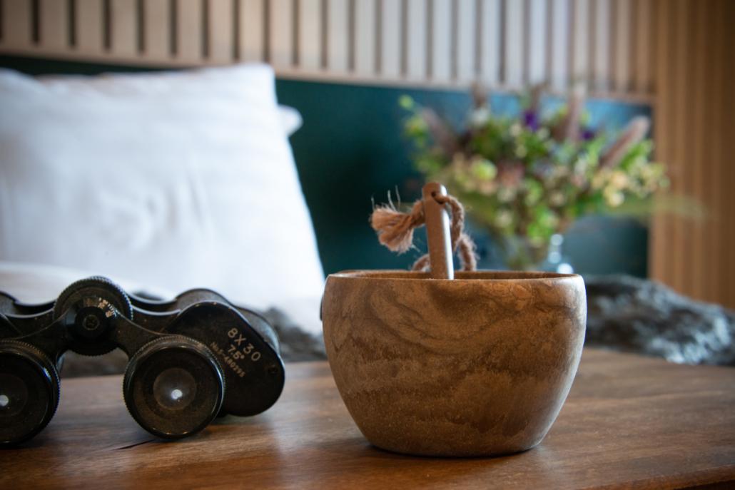 Hotellihuoneen sängyllä kupilka ja kiikarit