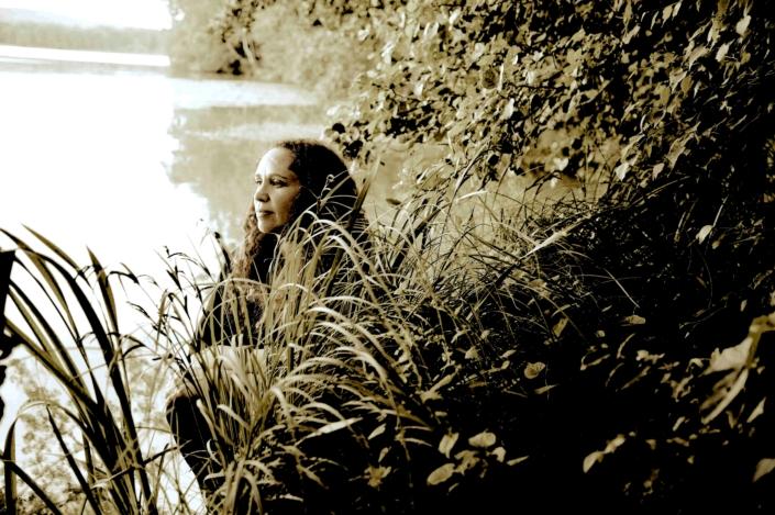 Nainen istuu rantaheinikossa